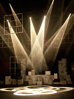 Several spot lights shining down on to a stage with props. Image bybigter choifromPixabay
